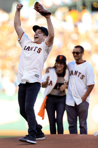 Zak Williams, the son of Robin Williams throws out the first pitch prior to  game 5 of the World Series in San Francisco, Sunday Oct. 26, 2014.   Siblings Zelda and Cody are in the background. (Kent Porter / Press Democrat) 2014