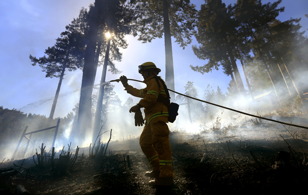 Monte Rio volunteer firefighter Gabriela Gibson, sprays down hot spots on a half acre fire in timber above Monte Rio, Friday April 10, 2015.  A control burn slopped over containment lines and wind blew embers in to the timber, igniting drought stressed trees and brush.  (Kent Porter / Press Democrat) 2015