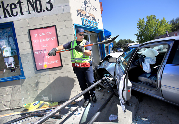 Sonoma Valley fire captain Mike Bruno helps to clean up glass from a market in Boyes Hot Springs Wednesday June 24, 2015, in which the driver of the car struck the building shattering the front door.  The driver sustained minor injuries. (Kent Porter / Press Democrat) 2015