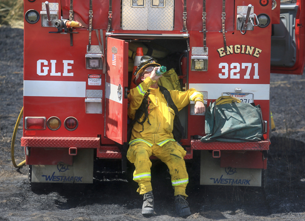 Glen Ellen firefighter George Psaledakis cools off after helping to contain a brush fire above the Petaluma valley floor on Sonoma Mountain, Tuesday June 30,  2015. (Kent Porter / Press Democrat) 2015