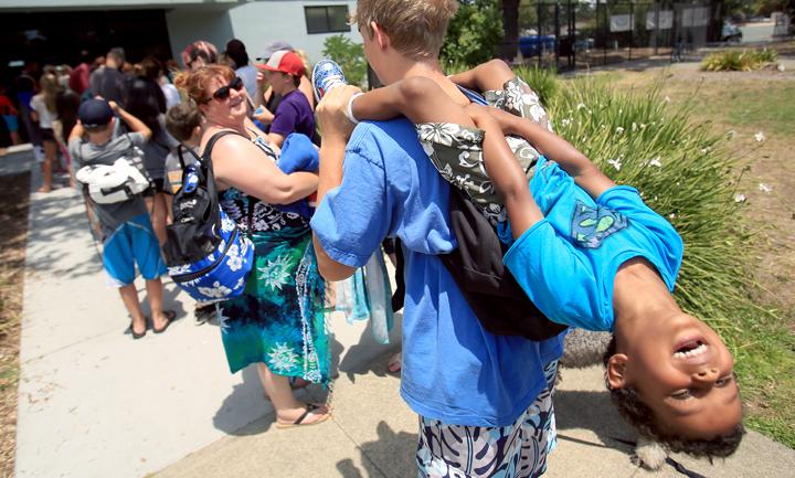 Noah Chock has a firm grasp on Tre Warren III as the wait for the Ridgeway Pool to open, Wednesday July 2, 2015. (Kent Porter / Press Democrat) 2015