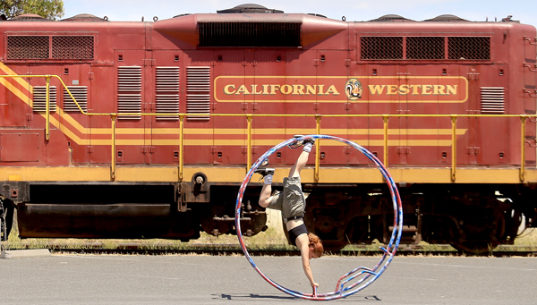 With a Skunk Train locomotive as a backdrop Tara Logan of Willits practices on a German Wheel for the upcoming Willits Fourth of July Parade, Thursday July 2, 2015. (Kent Porter / Press Democrat) 2015