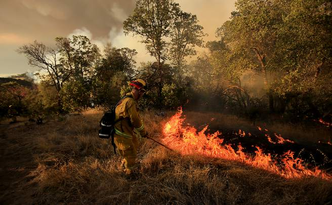 Smaller backfires were set by dragging burning brush to solidify containment lines on the Rocky Fire near Lower Lake  as they try to cut line around the perimeter of the fire, Wednesday July 29, 2015. (Kent Porter / Press Democrat) 2015
