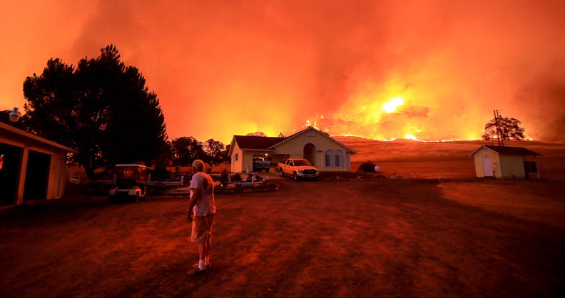 A wall of flames lurches over a ridge as a resident of Morgan Valley Road near Lower Lake prepares to evacuate the Rock Fire, Wednesday evening July 29, 2015. (Kent Porter / Press Democrat) 2015