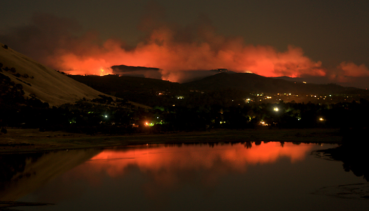The city of Clearlake is reflected, along with the Rocky Fire, in the waters of Borax Lake, above Clear Lake, Thursday morning  July 30, 2015.  The fire has grown to 8,000 acres since yesterday afternoon. (Kent Porter / Press Democrat) 2015