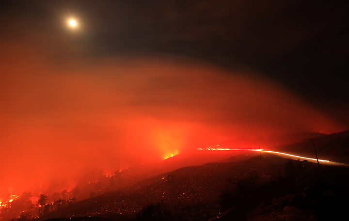 The Rocky Fire burns up and over a ridge underneath a full moon along Morgan Valley Road early Thursday morning  July 30, 2015.  The fire has grown to 8,000 acres since yesterday afternoon.  Lights from a strike team of engines can be seen on the right hand side in this long exposure. (Kent Porter / Press Democrat) 2015