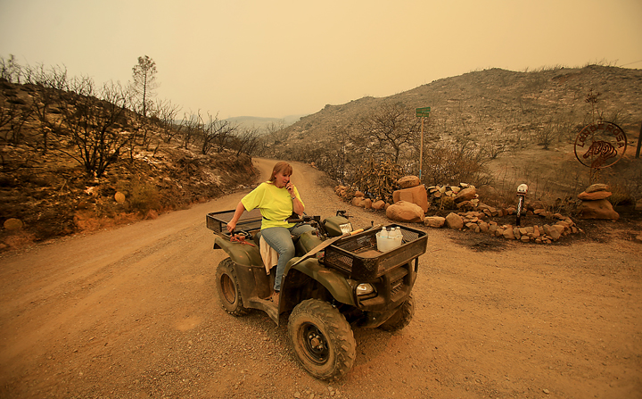 A moonscape greets Lonne Sloan at the corner of her driveway and Morgan Valley Road Thursday July 30, 2015 near Lower Lake as she calls 911 to report that fire was bearing down on her house once again. Sloan and her husband Larry stayed behind Wednesday night to put out flames around their home, even so it was touch and go, Sloan lost a barn, trailers and tractors to the Rocky Fire. (Kent Porter / Press Democrat) 2015
