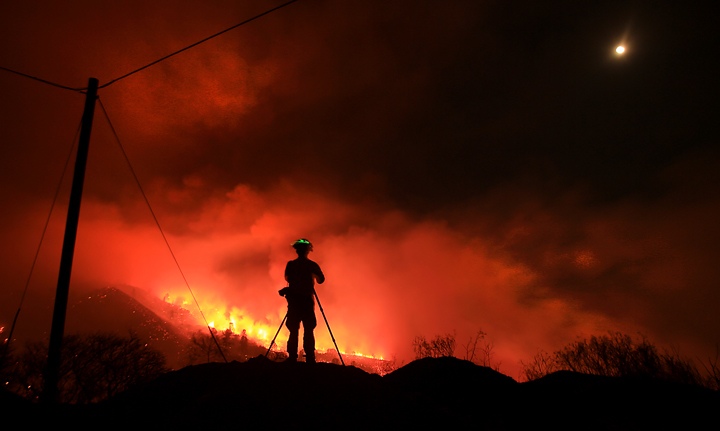 Southern California based fire photographer Stuart Palley photographs the Rocky Fire as it burns up and over a ridge along Morgan Valley Road early Thursday morning  July 30, 2015.  The fire has grown to 8,000 acres since yesterday afternoon. (Kent Porter / Press Democrat) 2015
