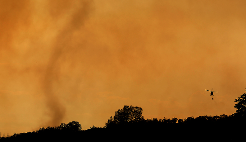 A wind driven smoke tornado dwarfs a water dropping helicopter on he Rocky fire, Thursday July 30, 2015 near Lower Lake . (Kent Porter / Press Democrat) 2015