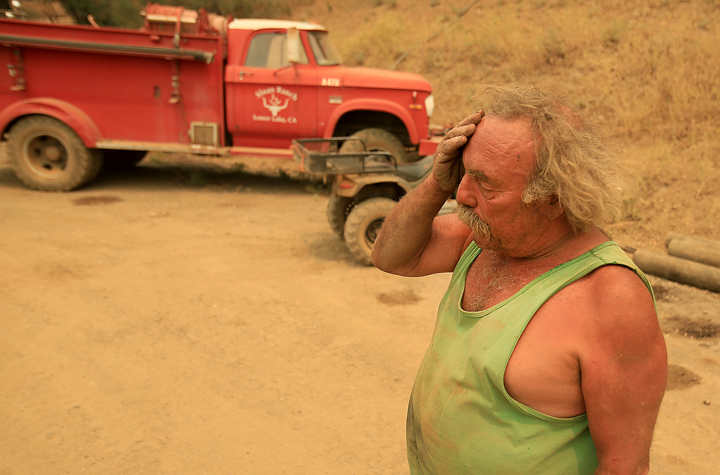 Larry Sloan protected his house with his own fire truck, background, at the height of the Rocky Fire Wednesday night near Lower Lake, Thursday July 30, 2015. (Kent Porter / Press Democrat) 2015