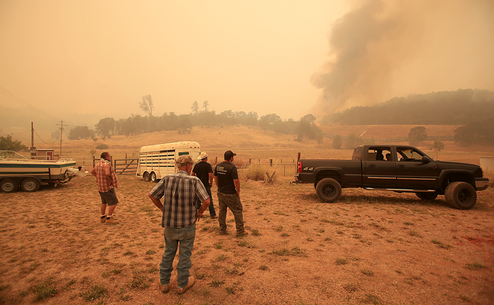 The Antonia family and friends watch as the Rocky Fire spots outside of containment lines, Thursday July 30, 2015 from their ranch off Morgan Valley Road. (Kent Porter / Press Democrat) 2015