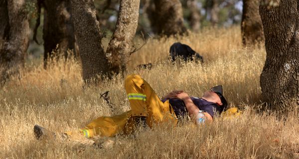 Tired firefighters find a comfortable spot to relax as they wait their next assignment on the Rocky fire, Wednesday Aug. 5, 2015. (Kent Porter / Press Democrat) 2015