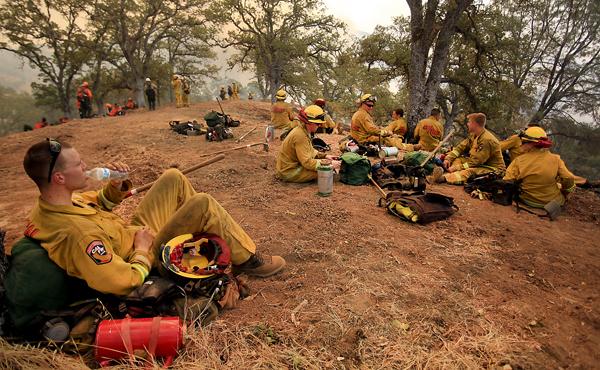 Cal Fire's Bryan King of the Tuolumne-Calaveras Unit relaxes as his strike team rests before cutting line at the top of the north side of the Jerusalem fire,  Monday Aug. 10, 2015.  (Kent Porter / Press Democrat) 2015
