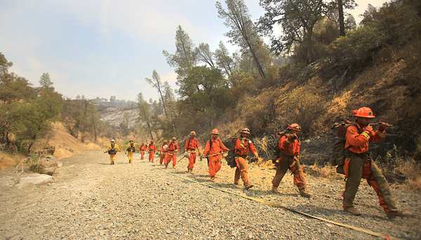 An inmate crew walks through a bone dry drought ravaged dry Soda Creek on their way to the the fire line as the Jerusalem fire continues to burn, Monday Aug. 10, 2015.  (Kent Porter / Press Democrat) 2015