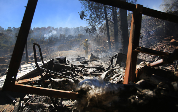 A Cal Fire firefighter who declined to give his name, douses hot spots around a trailer that was destroyed during the Grade fire off Jerusalem Valley Road in Lake County, Monday Aug. 24,  2015.  (Kent Porter / Press Democrat) 2015