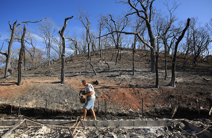 Bill Hilbrandie carries off his sisters computer hard drive from the remains of her home, destroyed by the Rocky Fire in Lake County, Tuesday Sept. 1,  2015.  (Kent Porter / Press Democrat) 2015