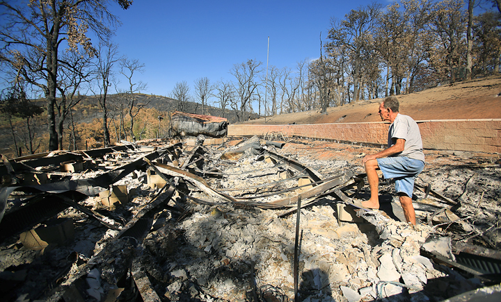 Bill Hilbrandie surveys what is left of his home, destroyed by the Rocky Fire in Lake County, Tuesday Sept. 1,  2015.  (Kent Porter / Press Democrat) 2015