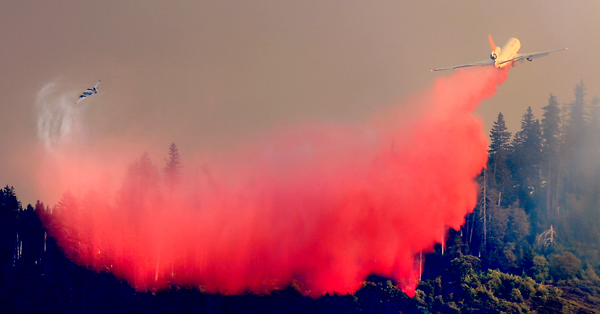 Tanke 912 makes a drop on the latest Lake County fire, the Elk fire, Wednesday Sept. 1, 2015.  (Kent Porter / Press Democrat) 2015