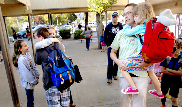 Cobb Elementary School was spared from the Valley fire (it sustained heat and smoke damage) still students are being re-routed to Middletown High and middle school to attend their classes. Cobb Elementary teacher Marc Morita and daughter Lily  Monday were accompanied to class by Heidi Hennek, and her daughter Gracelynn, embracing her nephew Beau Davis who lost his home to the blaze, Sept. 28, 2015.  (Kent Porter / Press Democrat) 2015