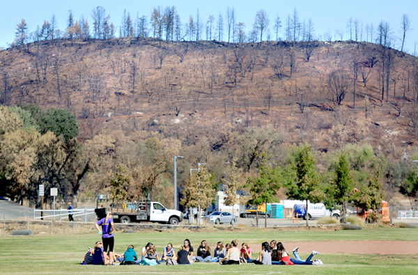 Middletown Middle School students meet on the athletic fields to talk about the Valley fire, on the first day of classes since the disaster started. A stark reminder of the devastation to the area can be seen in the background, Monday Sept. 28, 2015.  (Kent Porter / Press Democrat) 2015