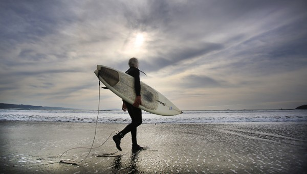 63 year-old Eddie Scanlon of Petaluma heads out to the Doran Park surf, Tuesday Jan. 12, 2016 in Bodega Bay.  (Kent Porter / Press Democrat) 2016