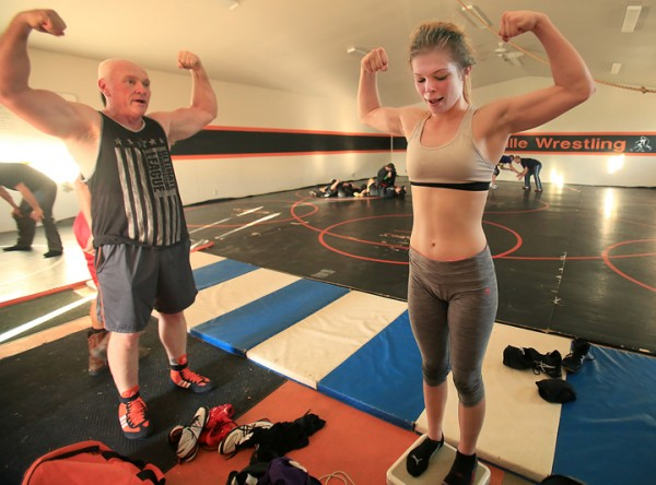With persuasion from Kelseyville High School Coach and Lake County Supervisor, Rob Brown,  Upper Lake High School sophomore wrestler Christina Wilson shows her form after making weight Wednesday Feb. 24, 2016 after an all county workout at Kelseyville High School. Wilson is headed to state after winning the NCS title in the 121 pound class.  (Kent Porter / Press Democrat) 2016