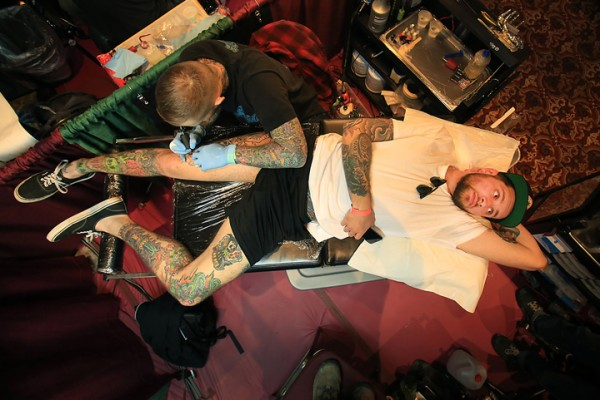 Jeremy Sarayi of Santa Jose has  his tattoo worked on by Tiny Jim Herman of Washington, during the Tattoos and Blues at the Flamingo Hotel in Santa Rosa, Friday Feb. 26, 2016. (Kent Porter / Press Democrat) 2016Jeremy Sarai