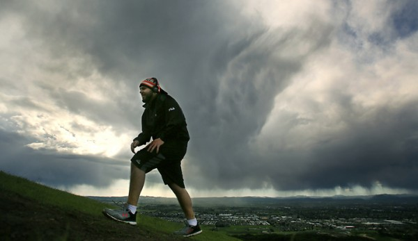 Storm clouds add a dramatic flair as Trevor Shatara takes a hike at Taylor Mountain Regional Park and Open Space Preserve Monday March 28, 2016. (Kent Porter / Press Democrat) 2016