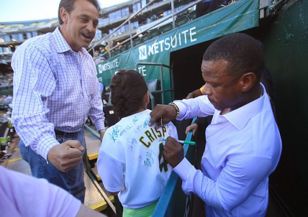 Emma Hatcher, 12, gets an autograph from Rickey Henderson as her dad Jeff Hatcher celebrates prior to the A's opener against the White Sox,  Monday April 4, 2016.  The two are from Livermore. (Kent Porter / Press Democrat ) 2016