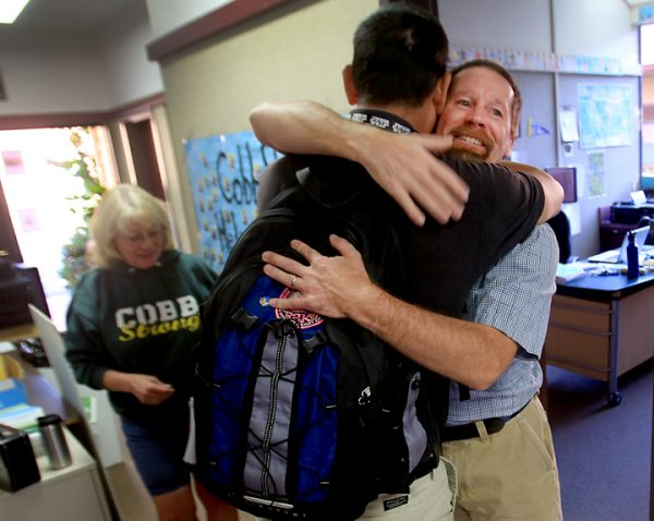 During Cobb Elementary's first day of School, Wednesday Aug. 10, 2016 principal David Leonard, right, greets sixth grade teacher Marc Moreda. Leonard lost his home to the Valley Fire a year ago. At right is school secretary Karen Huff. (Kent Porter / The Press Democrat) 2016