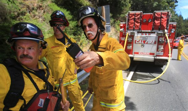 Fire Chief Steve Baxman, 46-year volunteer with Monte Rio Fire, talks with Cal Fire Battalion Chief Mark Gradek, left, and Cal Fire captain Chris Rickert as they discuss which engines to release from a vegetation fire along Highway 116 in Monte Rio, Friday July 15, 2016. (Kent Porter / Press Democrat) 2016