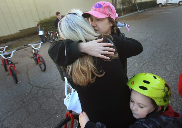 Nichole McCarty and her son Jeremiah Bishop ,6, give a heartfelt and tearful embrace to Bishop's Thomas Page Elementary school teacher Teresa Peterson, after McCarty's children were put on a list to receive new bikes from Innovative Screen Printing and Embroidery in Rohnert Park, Friday Dec. 16, 2016. (Kent Porter / The Press Democrat) 2016